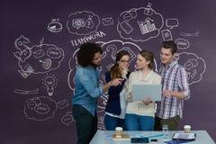 Executivos felizes em uma mesa que olha um computador contra o fundo roxo com gráficos Fotos de Stock