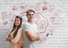 Executivos felizes que estão contra a parede branca com gráficos Imagens de Stock