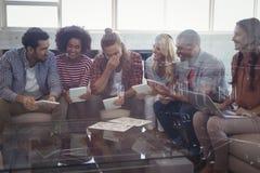 Executivos felizes que trabalham ao sentar-se junto no escritório criativo Fotografia de Stock