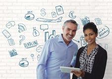 Executivos felizes que usam uma tabuleta contra a parede branca com gráficos Fotos de Stock Royalty Free