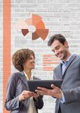 Executivos felizes que usam uma tabuleta contra a parede branca com gráficos Foto de Stock