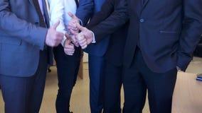 Executivos irreconhecíveis que mostram seus polegares acima filme