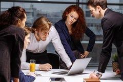 Executivos masculinos e fêmeas em torno do laptop no escritório fotografia de stock royalty free
