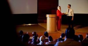executivos Multi-étnicos que agitam a mão na fase no seminário do negócio no auditório 4k video estoque
