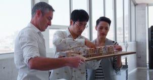 executivos Multi-étnicos que discutem sobre o modelo da fábrica no escritório moderno 4k filme