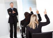 Executivos na leitura que fazem perguntas Imagens de Stock Royalty Free