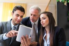 Executivos no trabalho com tabuleta Fotos de Stock