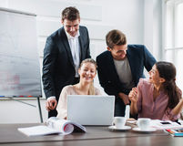 Executivos novos bem sucedidos que usam o portátil na mesa no escritório Fotos de Stock