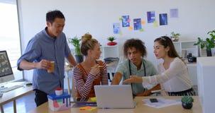 Executivos novos da misturado-raça que trabalham no portátil e que interagem cada outro em um escritório 4k vídeos de arquivo