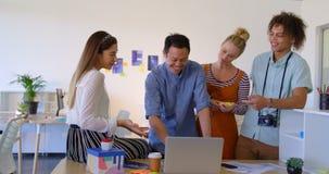 Executivos novos da misturado-raça que trabalham no portátil na mesa no escritório moderno e que riem junto 4k filme