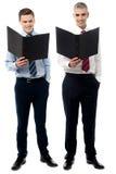 Executivos novos de sorriso com dobrador imagem de stock
