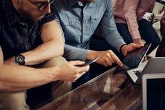 Executivos novos do grupo três recolhidos junto discutindo o café moderno da ideia criativa Colegas de trabalho que encontram uma Fotos de Stock Royalty Free