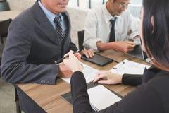 Executivos novos e empresário que têm uma reunião em torno de t Imagens de Stock