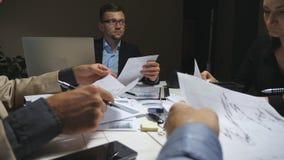 Executivos novos que sentam-se na tabela e que discutem cartas e gráficos da renda no fim do dia de trabalho Equipe do neg?cio filme