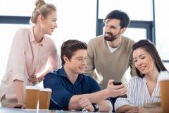 Executivos novos que usam o smartphone na reunião de negócios pequena fotografia de stock