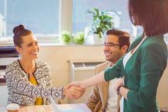 Executivos ocasionais que agitam as mãos na mesa e no sorriso Fotografia de Stock