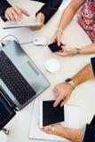 Executivos ocasionais que usam objetos eletrônicos diferentes em um meetin Fotografia de Stock Royalty Free