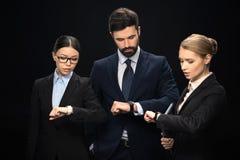 Executivos pensativos que estão e que olham os relógios isolados no preto Fotos de Stock