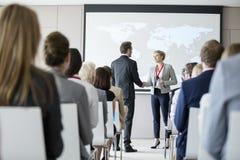 Executivos que agitam as mãos durante o seminário no centro de convenções fotos de stock royalty free
