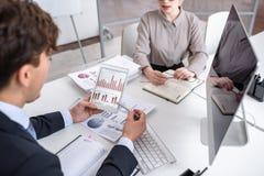 Executivos que analisam o relatório do mercado e da finança imagem de stock