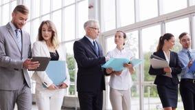 Executivos que andam ao longo do prédio de escritórios 9 video estoque