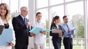 Executivos que andam ao longo do prédio de escritórios 8 video estoque