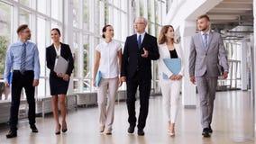 Executivos que andam ao longo do prédio de escritórios 6 vídeos de arquivo