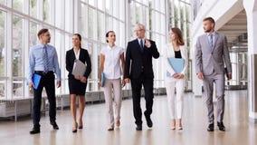 Executivos que andam ao longo do prédio de escritórios 7 video estoque