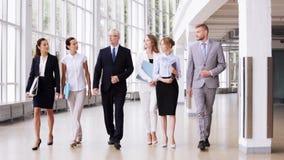 Executivos que andam ao longo do prédio de escritórios 2 video estoque