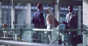 Executivos que andam com bagagem no corredor no escritório 4k vídeos de arquivo