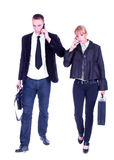 Executivos que andam e que convidam o móbil. Imagens de Stock Royalty Free