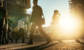 Executivos que andam em uma rua movimentada cedo na manhã fotos de stock royalty free