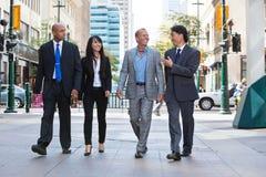 Executivos que andam junto na rua Fotografia de Stock