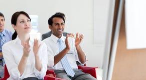 Executivos que aplaudem em uma conferência imagem de stock