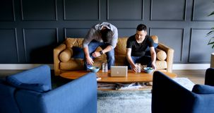 Executivos que comem o alimento no sofá 4k video estoque