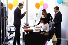 Executivos que comemoram a festa de anos do colega no escritório Fotos de Stock Royalty Free
