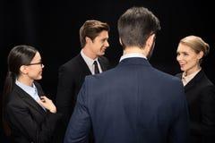 Executivos que conectam e que estão no estúdio isolado no preto Fotos de Stock