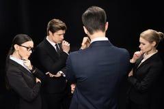 Executivos que conectam e que estão no estúdio isolado no preto Fotos de Stock Royalty Free