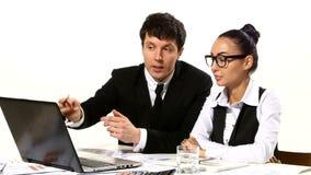 Executivos que discutem as ideias que olham o portátil vídeos de arquivo