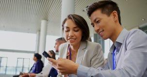 Executivos que discutem sobre o telefone celular no seminário 4k do negócio video estoque