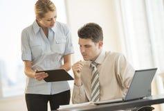Executivos que discutem sobre a tabuleta de Digitas no escritório fotos de stock