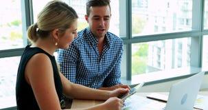 Executivos que discutem sobre a tabuleta digital no escritório filme