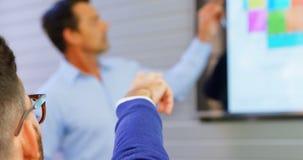 Executivos que discutem sobre a tela do lcd na sala de conferências 4k filme