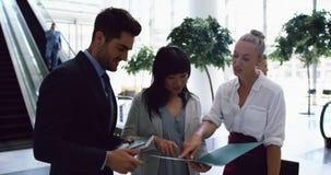 Executivos que discutem sobre um arquivo na entrada no escritório 4k vídeos de arquivo