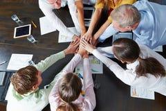 Executivos que empilham as mãos como o conceito dos trabalhos de equipa imagem de stock royalty free