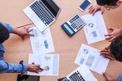 Executivos que encontram-se no conceito do escritório, usando ideias, cartas, computadores, tabuleta, dispositivos espertos no pl imagem de stock