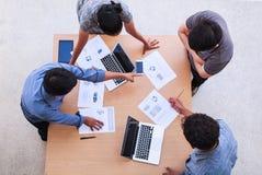 Executivos que encontram-se no conceito do escritório, usando ideias, cartas, computadores, tabuleta, dispositivos espertos no pl imagens de stock