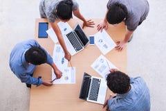 Executivos que encontram-se no conceito do escritório, usando ideias, cartas, computadores, tabuleta, dispositivos espertos no pl fotografia de stock