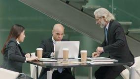 Executivos que encontram-se no escritório usando o laptop video estoque