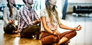 Executivos que executam a ioga no assoalho imagem de stock royalty free